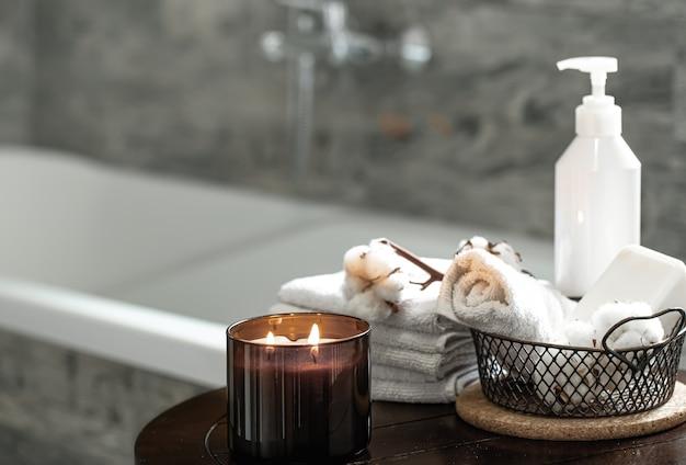 Interno del bagno sfocato, candela accogliente e set di asciugamani piegati puliti.