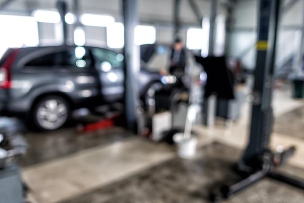 Sfocato del tecnico automobilistico che ripara l'auto sullo sfondo del garage, interno di una stazione di riparazione auto
