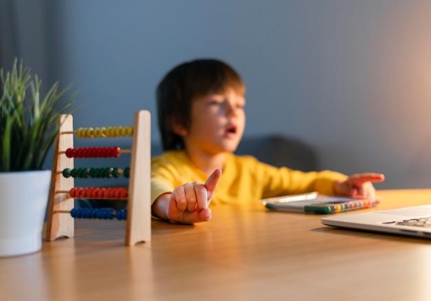 Bambino sfocato che segue corsi virtuali