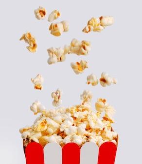 Popcorn caduta offuscata dall'alto nel secchio di carta a strisce di popcorn, su sfondo chiaro.
