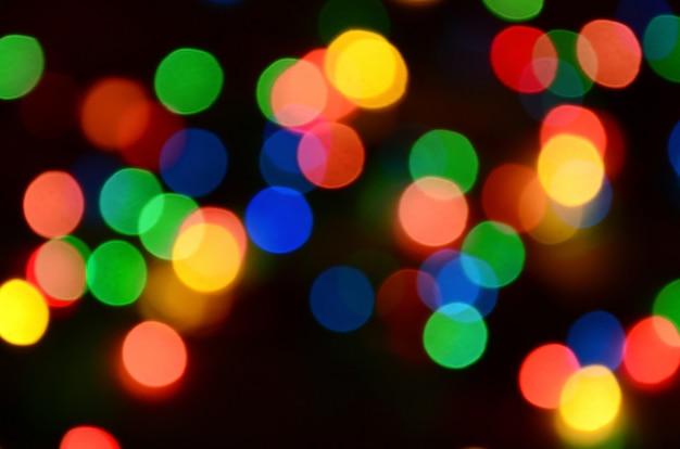 Offuscata luci colorate festive su nero utile come sfondo