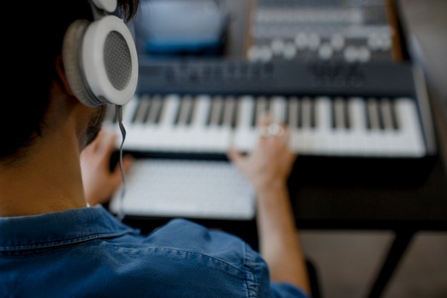 Primo piano sfocato di messa a fuoco. l'arrangiatore maschio di musica passa la composizione della canzone sul piano del midi e sull'audio attrezzatura in studio di registrazione digitale. l'uomo produce la colonna sonora elettronica o la traccia nel progetto a casa
