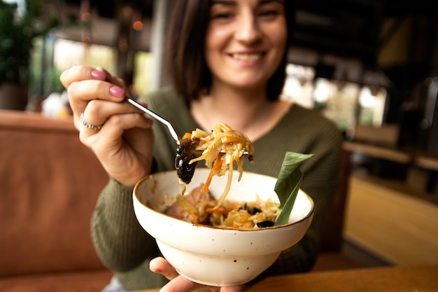 Donna felice vaga che mostra il suo pasto gustoso e sorridente. concetto di cibo asiatico.
