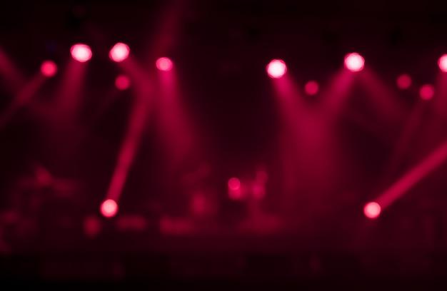 Immagine sfocata sullo sfondo delle luci rosse del palcoscenico. concetto di festa, concerto e intrattenimento