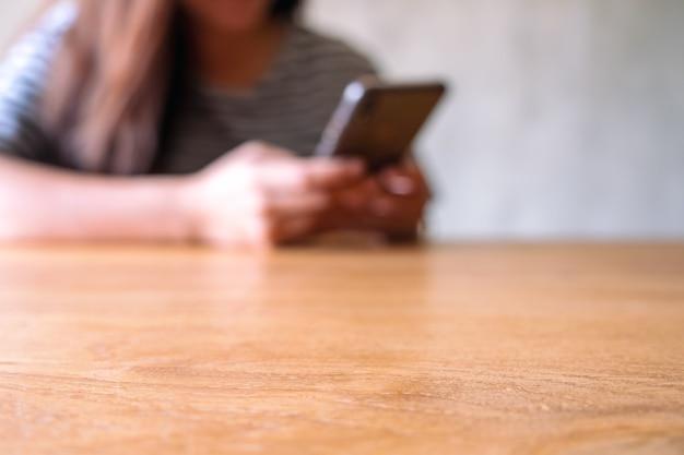 Immagine sfocata di una donna che tiene in mano, usa e guarda il cellulare