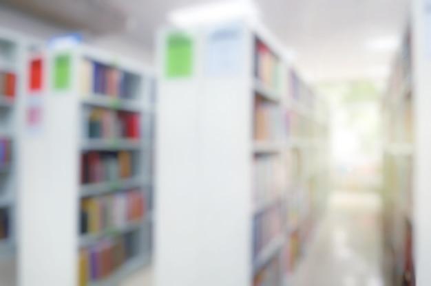 Sfocato dell'interno della biblioteca pubblica con libri in scaffali di legno. educazione e giornata del libro.