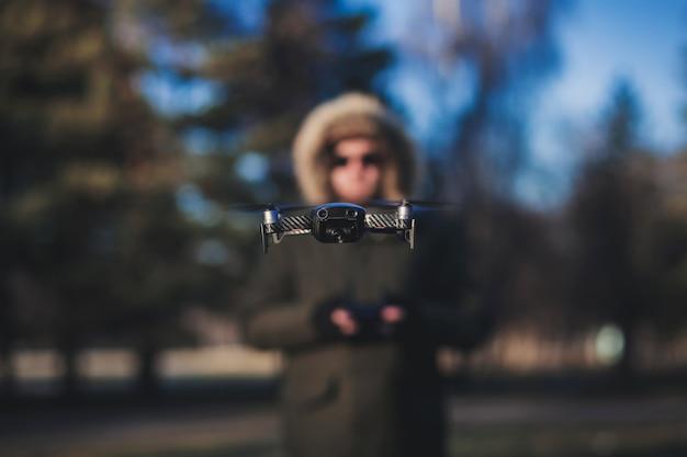 Uomo sfocato sullo sfondo di un drone volante.