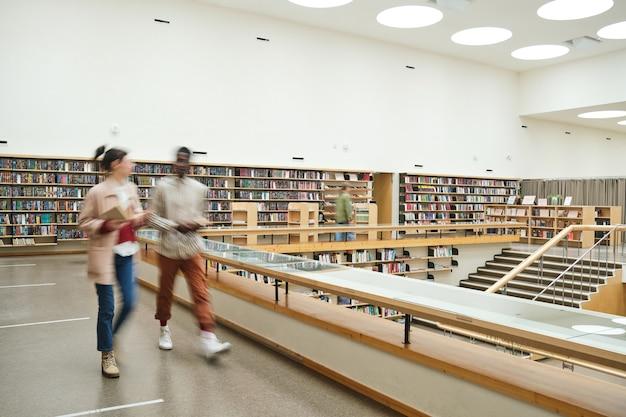 Movimento sfocato di persone che camminano lungo il corridoio nella grande biblioteca