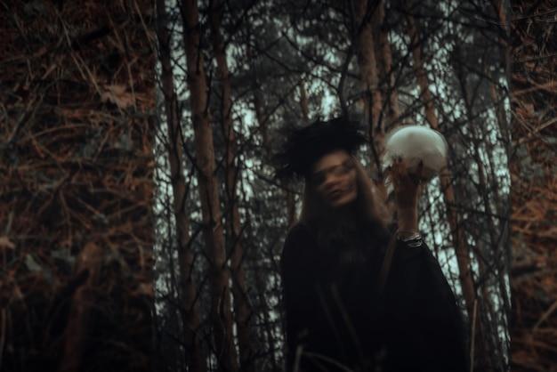 Sfocato riflesso mistico nello specchio di una strega spaventosa malvagia con il cranio di un uomo morto che evoca rituali mistici occulti nella foresta