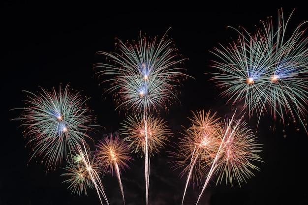 Fuochi d'artificio variopinti vaghi del nuovo anno sulla celebrazione del cielo nero