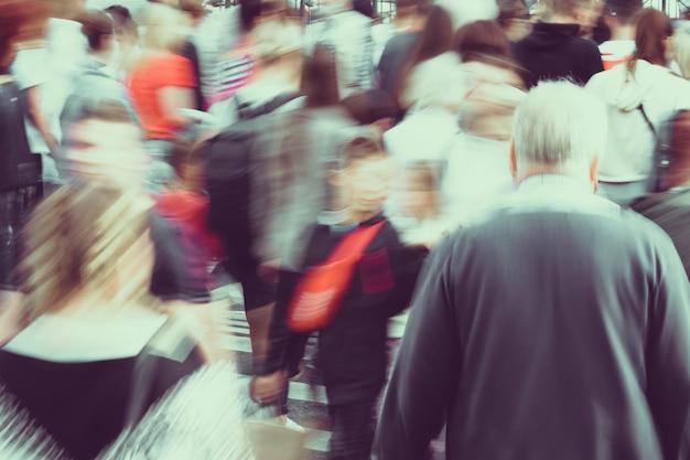 Persone sfocate che attraversano le strade della città con tonica