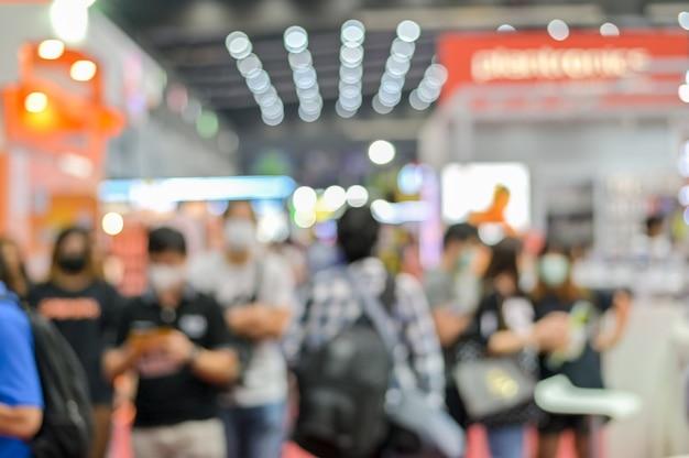 La gente vaga cammina alla fiera di mostra della sala commerciale del corridoio con la maschera d'uso