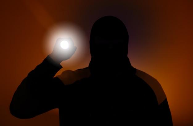 Foto sfocata. ladro in abiti scuri che tiene la torcia. ladro pericoloso in maschera con una torcia. uomo criminale.