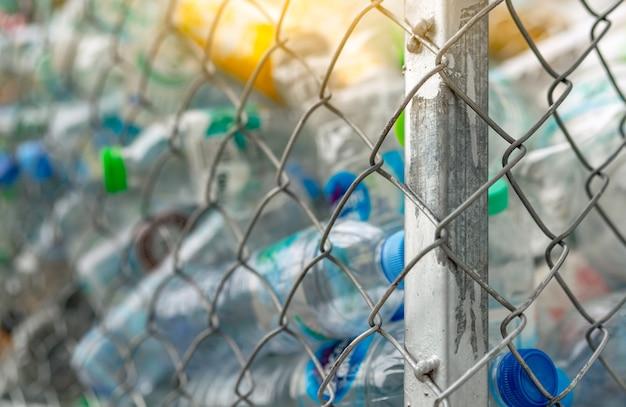 Mucchio sfocato della bottiglia di plastica dell'acqua vuota nel cestino del recinto. rifiuti di bottiglie di plastica per il riciclaggio.
