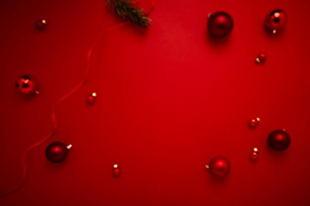 Decorazione rossa sfocata di palline di natale su sfondo rosso di carta con spazio per copia per capodanno e buon natale
