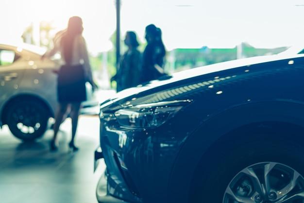 Commessa e acquirente sfocati nello showroom di lusso concessionaria auto nuova auto parcheggiata nello showroom moderno