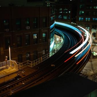 Inquadratura sfocata di un treno passeggeri che passa di notte