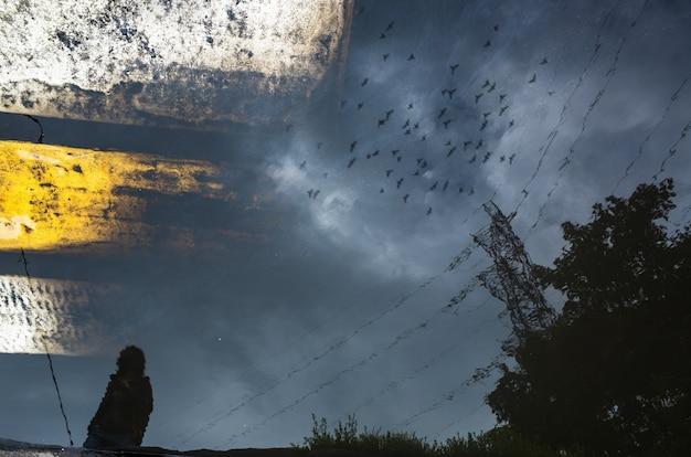 Sagoma sfocata del riflesso di una persona che cammina da sola sul marciapiede bagnato della città in una giornata piovosa