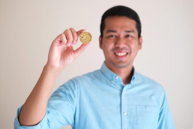 Volto di uomo d'affari asiatico sorridente sfocato che mostra la sua moneta d'oro con chip elettronico