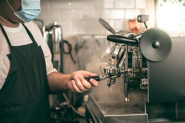 Immagini sfocate morbide dell'uomo asiatico barista caffè, indossare una mascherina chirurgica prevenire la malattia