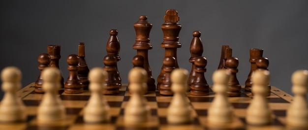 Pedine bianche offuscate contro un gruppo di figure di scacchi nere sulla scacchiera.