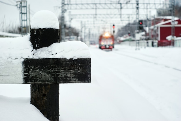 Paesaggio invernale sfocato di un nodo ferroviario con un frammento di una fermata del buffer