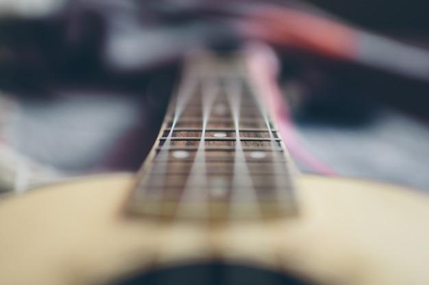 Chitarra acustica in legno sfocata con quattro corde