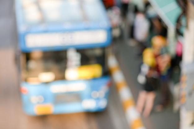 Blurry blue bus raccoglie i passeggeri alla stazione degli autobus.