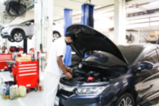 Stazione di riparazione auto sfocata e riparatore che lavora in garage. manutenzione dell'auto o controllo del concetto di riparazione dell'auto.