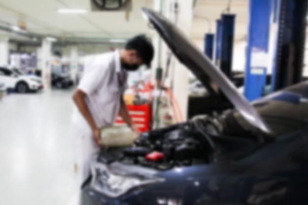 Stazione di riparazione auto sfocata e riparatore che lavora in garage concetto di manutenzione auto