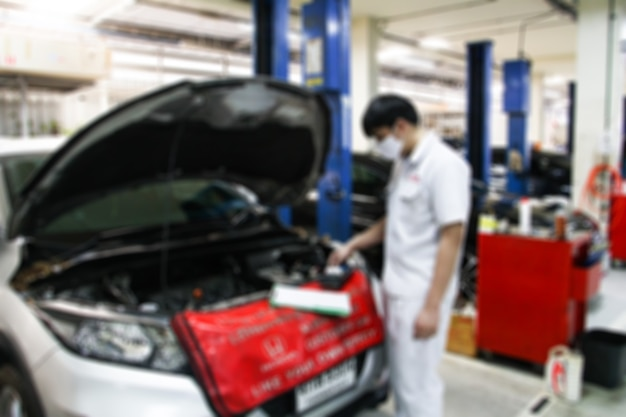 Stazione di riparazione auto sfocata e riparatore che lavora nell'officina del garage
