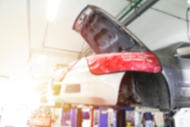 Stazione di riparazione auto sfocata e riparatore che lavora in garage.