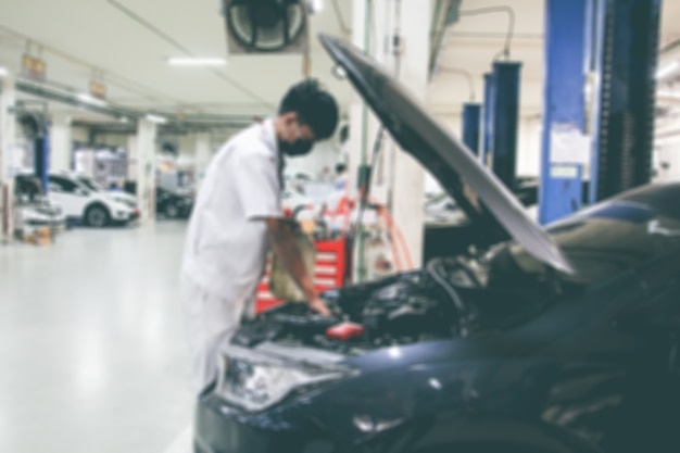 Stazione di riparazione auto sfocata e riparatore che lavora con l'auto a motore nell'officina del garage