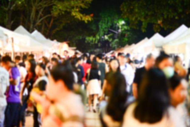 Folla sfocata sfocata di shopping a piedi anonimo sul mercato notturno.