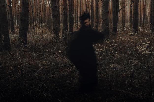 Siluetta nera spaventosa sfocata di una strega cattiva in una foresta oscura