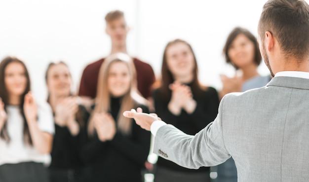 Immagine sfocata di un gruppo di persone diverse in piedi in una sala conferenze