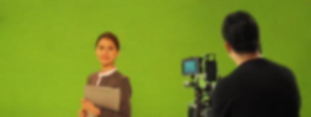 Immagini sfocate di realizzare video di film commerciali tv in un grande sfondo dello schermo verde. team di troupe cinematografica che lavora con l'attore. registrazione con fotocamera digitale professionale e set di illuminazione. film dietro le quinte