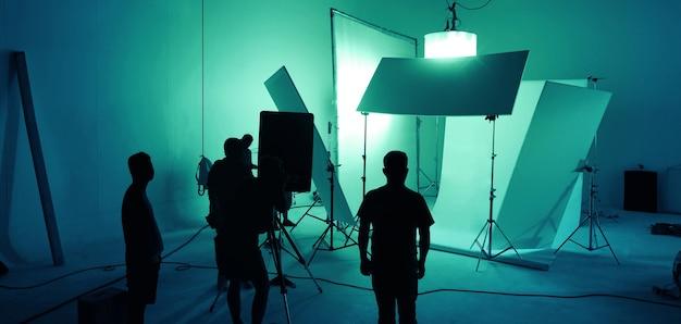 Immagini sfocate del team di produzione vdo che lavora in uno studio fotografico con sfondo e luce