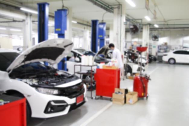 Linea sfocata di carrozzeria car con la stazione di riparazione dell'attrezzatura nell'officina del garage. fissare la manutenzione o il controllo da officina meccanica. affari sul concetto di auto o veicolo.