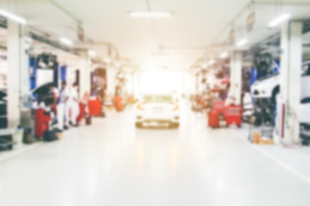 Linea sfocata della carrozzeria dell'auto con la stazione di riparazione dell'attrezzatura nell'officina del garage