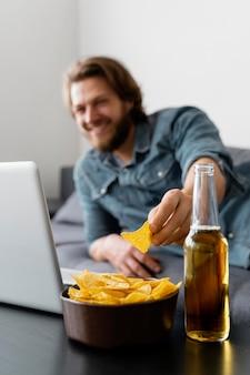 Uomo sfocato sul divano con patatine