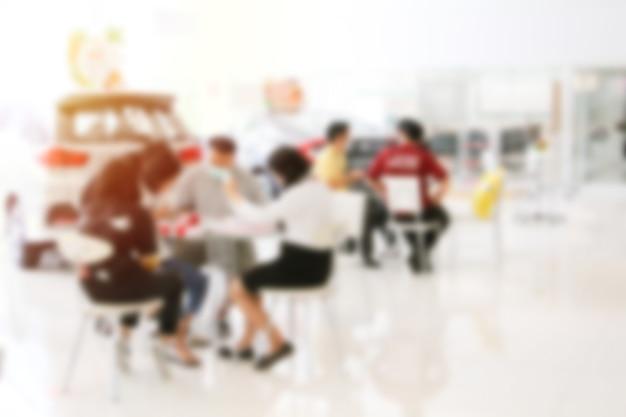 Sfocate molte riunioni anonime della folla sul tavolo. incontro e parlare con il concetto di consumatore.