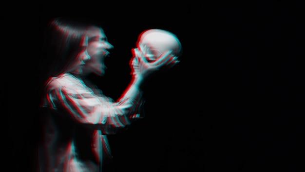 Sfocato terribile ritratto di una strega fantasma con il teschio di un uomo morto tra le mani su uno sfondo scuro. in bianco e nero con effetto di realtà virtuale glitch 3d