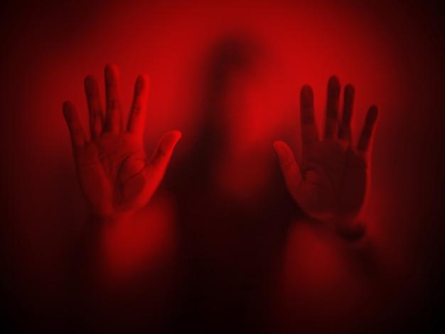 Mano sfocata della donna dietro il panico della metafora del vetro smerigliato ed emozione scura negativa
