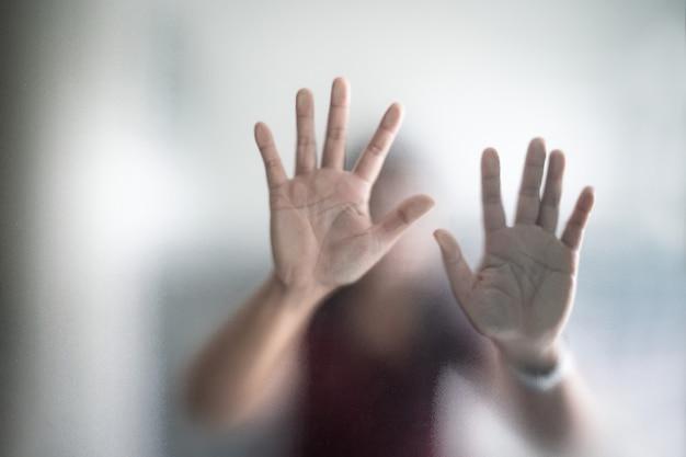 Mano sfocata della donna dietro il panico della metafora di vetro smerigliato ed emozione scura negativa