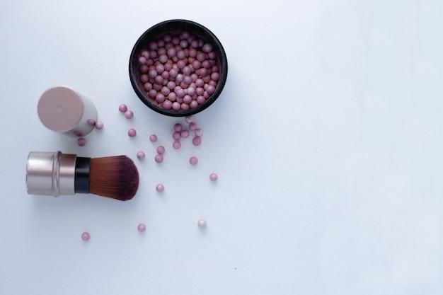 Palline di fard di colore rosa e crema e un pennello per applicare il fard su uno sfondo bianco con un plac...