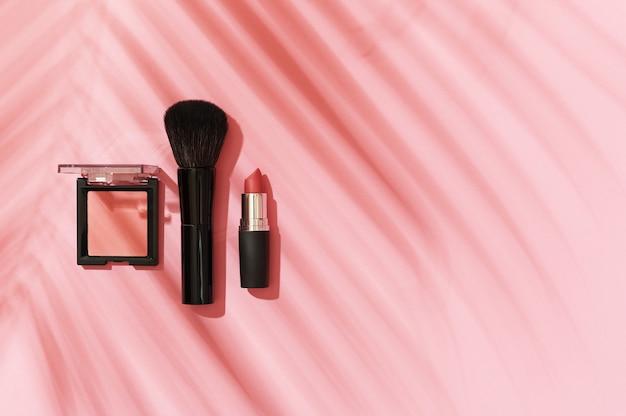 Fard, pennello per il trucco, rossetto su uno sfondo rosa con un'ombra da una vista dall'alto di una foglia di palma. concetto di trucco estivo, prodotti di bellezza per donna, accessori. copia spazio, piatto.