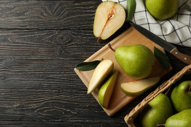 Pensione e cestino con pere verdi su legno