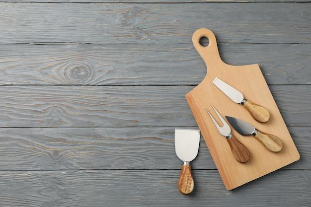 Coltelli da tavola e formaggio su legno