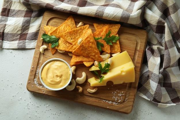Tavola con salsa di formaggio e snack su tavola bianca testurizzata